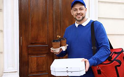 Lierfbote der für Kundentüre steht und Pizza ausliefert